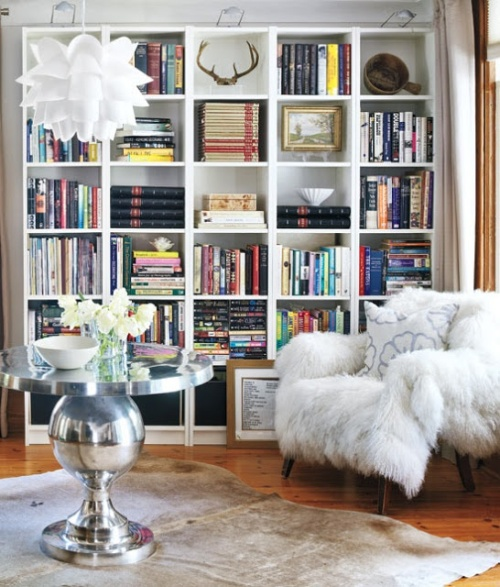 A white fur throw brings cozy to an arm chair in this stylish little  library. Contributing to the glam feel is shiny round metal table topped  with a pure ...